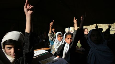 """Girls at the Bibi Mahroo High School raise their hands during an English class in Kabul in November 2006. After the fall of the Taliban, millions of Afghan girls <a href=""""https://www.cnn.com/2012/09/26/world/asia/cnnheroes-afghan-schoolgirls"""" target=""""_blank"""">were able to attend school</a> and get the education that their mothers couldn't."""