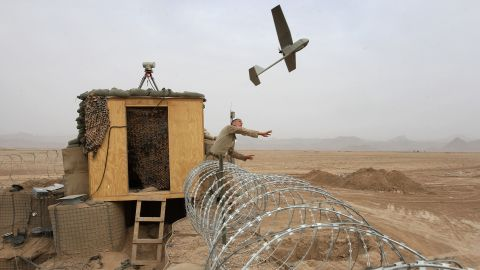 US Marine Sgt. Nicholas Bender launches a Raven surveillance drone near the remote village of Baqwa, Afghanistan, in March 2009.