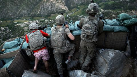 """US soldiers take defensive positions after receiving fire from Taliban positions in Afghanistan's Korengal Valley in May 2009. Army Spc. Zachary Boyd was still in his """"I love NY"""" boxers because he rushed from his sleeping quarters to join his fellow platoon members."""