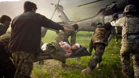Afghan soldiers rush a wounded police officer to an American helicopter in Afghanistan's Kunar province in March 2010.