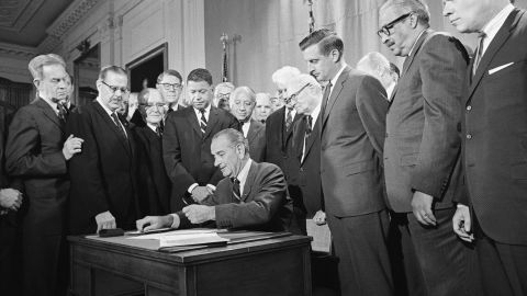 Mondale and other senators watch as Johnson signs the Civil Rights Act of 1968 into law on April 11, 1968.