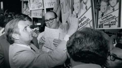 Mondale signs a poster of him and Carter while campaigning in New York on October 4, 1976.