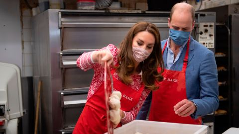 Will watches as Kate pours a tray of bagel dough into a container during a visit to Beigel Bake Brick Lane Bakery in London, on September 15, 2020.