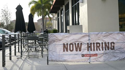 A Now Hiring banner sign is viewed outside a Chipotle restaurant during a new coronavirus pandemic, Tuesday, March 2, 2021, in Orlando, Fla. (Phelan M. Ebenhack via AP)