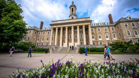 Students and adults walk in front of the Old Main building, on the campus of Penn State University, in State College, Pennsylvania.