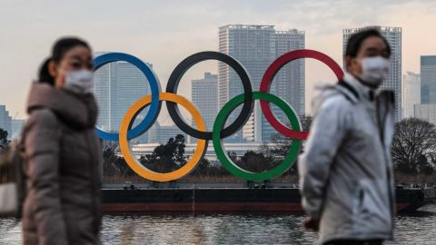 TOKYO, JAPAN - JANUARY 22: People wearing face masks walk past the Olympic Rings on January 22, 2021 in Tokyo, Japan. With just six months to go until the start of the Games, it has been reported that the Japanese authorities have privately concluded that the Olympics could not proceed due to the ongoing Covid-19 coronavirus pandemic. Spokesmen from the IOC and Japanese government have since rejected the report. (Photo by Carl Court/Getty Images)