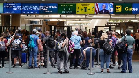 Travelers line up to go through a TSA checkpoint at Orlando International Airport before the Memorial Day weekend on Friday, May 28, 2021, in Florida.