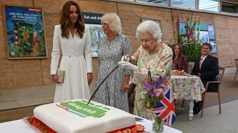 TOPSHOT - Britain's Queen Elizabeth II (C) attempts to cut a cake with a sword, lent to her by The Lord-Lieutenant of Cornwall, Edward Bolitho, to celebrate of The Big Lunch initiative at The Eden Project, near St Austell in south west England on June 11, 2021. (Photo by Oli SCARFF / POOL / AFP) (Photo by OLI SCARFF/POOL/AFP via Getty Images)