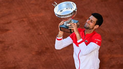 TOPSHOT - Serbia's Novak Djokovic poses with The Mousquetaires Cup (The Musketeers) after winning against Greece's Stefanos Tsitsipas at the end of their men's final tennis match on Day 15 of The Roland Garros 2021 French Open tennis tournament in Paris on June 13, 2021. (Photo by MARTIN BUREAU / AFP) (Photo by MARTIN BUREAU/AFP via Getty Images)