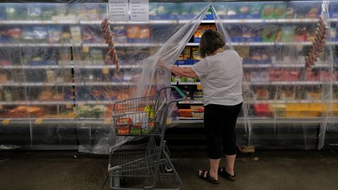 A woman shops for perishable items at a grocery store in Portland on Monday. The food was covered with a layer of plastic to keep in the cool air.