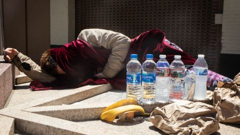 A man experiencing homelessness sleeps in the Portland sun on Monday. Nonprofit groups have also been opening cooling centers to help people in Portland and other Oregon cities.