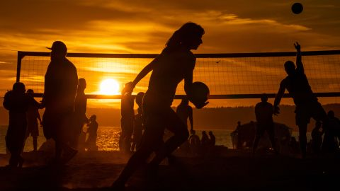 People play beach volleyball at Seattle's Golden Gardens Park as the sun sets on Thursday.
