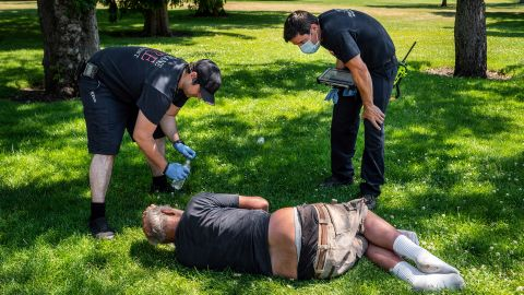 Firefighters check on a man in Spokane's Mission Park on Tuesday.