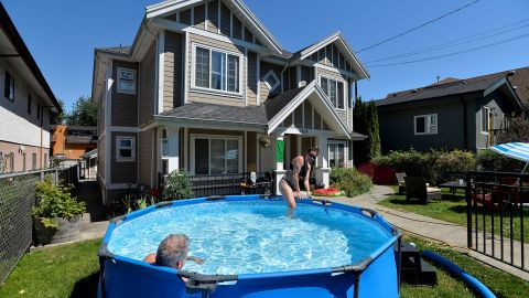 Emily Beers and Craig Patterson cool off Sunday in a pool set up in front of Patterson's home in Vancouver, British Columbia.