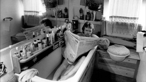 Branson reads the newspaper in a bathtub aboard his houseboat in London in 1984.