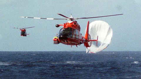 US Coast Guard helicopters head back to the Barbers Point Naval Air Station in Hawaii after rescuing Branson and his co-pilots following a hot-air balloon crash in 1998. Branson and his co-pilots were attempting to fly around the world in a hot-air balloon. They started in Morocco and passed through Asia before eventually crash-landing in Hawaii. No one was hurt.