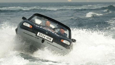 Branson, left, pilots an amphibious vehicle during a record-breaking crossing of the English Channel in 2004. He crossed the channel in one hour, 40 minutes and six seconds.