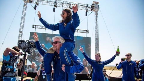 """Branson carries crew member Sirisha Bandla on his shoulders while celebrating after their <a href=""""https://www.cnn.com/2021/07/11/us/gallery/richard-branson-space-flight/index.html"""" target=""""_blank"""">historic spaceflight</a> in July 2021. Branson became the first billionaire to travel to space aboard a spacecraft he helped fund. Bandla is the second woman born in India to fly to space."""