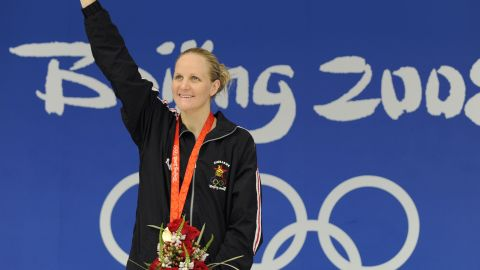 Gold medalist Zimbabwe's Kirsty Coventry stands on the podium for the women's 200m backstroke swimming final medal ceremony at the National Aquatics Center during the 2008 Beijing Olympic Games in Beijing on August 16, 2008.    Kirsty Coventry of Zimbabwe set a new world record in the women's 200 metres backstroke with a time of two minutes 05.24 seconds in the final at the Beijing Olympics. US swimmer Margaret Hoelzer placed second and Japanese swimmer Reiko Nakamura placed third.  AFP PHOTO / TIMOTHY CLARY (Photo credit should read TIMOTHY CLARY/AFP via Getty Images)