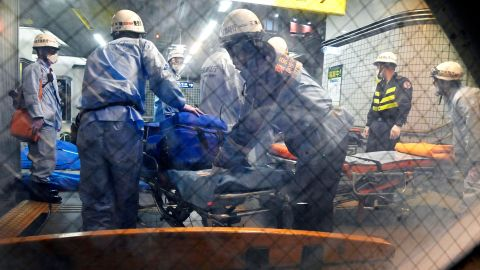Emergency workers prepare stretchers at Soshigaya Okura Station in Tokyo after a stabbing on a commuter train on Friday left at least 10 people injured.