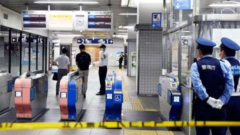 Policemen stand as ticket gates are sealed off at Soshigaya-Okura Station after a stabbing on a commuter train in Tokyo on Friday.