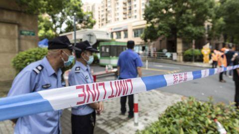 Politie, bewakers en vrijwilligers helpen bij het afzetten van een wijk die op 3 augustus 2021 in Shanghai, China, was afgesloten nadat een bewoner positief was getest op Covid-19.