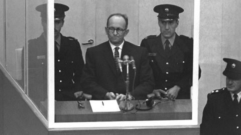 JERUSALEM, ISRAEL: (FILE PHOTO) Nazi war criminal Adolph Eichmann stands in a protective glass booth flanked by Israeli police during his trial April 5, 1961 in Jerusalem. The Israeli police donated Eichmann's original handprints, fingerprints and mugshot to Jerusalem's Yad Vashem Holocaust memorial ahead of Israel's annual Holocaust remembrance day May 4, 2005 which this year also marks the 60th anniversary of the Nazi's World War II defeat in 1945. (Photo by GPO via Getty Images)