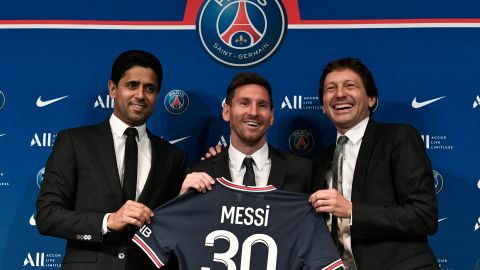 TOPSHOT - Paris Saint-Germain's Qatari President Nasser Al-Khelaifi (L) and Paris Saint-Germain's Sporting Director Leonardo Nascimento de Araujo (R) pose along side Argentinian football player Lionel Messi (C) as he holds-up his number 30 shirt during a press conference at the French football club Paris Saint-Germain's (PSG) Parc des Princes stadium in Paris on August 11, 2021. - The 34-year-old superstar signed a two-year deal with PSG on August 10, 2021, with the option of an additional year, he will wear the number 30 in Paris, the number he had when he began his professional career at Spain's Barca football club. (Photo by STEPHANE DE SAKUTIN / AFP) (Photo by STEPHANE DE SAKUTIN/AFP via Getty Images)