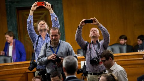 Photographers use iPhones to take photos of Cook during a break in a Senate hearing held by the Homeland Security and Governmental Affairs Subcommittee on Investigations on May 21, 2013. Cook and other Apple officials were on hand to explain the company's filings after the subcommittee accused Apple of tax avoidance.