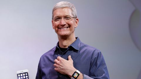 Cook, holding an iPhone 6 Plus and wearing an Apple Watch, discusses the new products during an event in Cupertino on September 9, 2014.