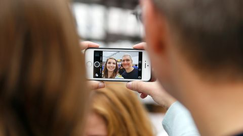 Cook, right, takes a photo with an Apple employee during the launch of the iPhone 6 at an Apple store in Palo Alto, California, on September 19, 2014.