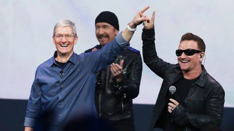 Cook greets the crowd with U2 singer Bono as U2 guitarist The Edge looks on during an Apple special event at the Flint Center for the Performing Arts in Cupertino on September 9, 2014.