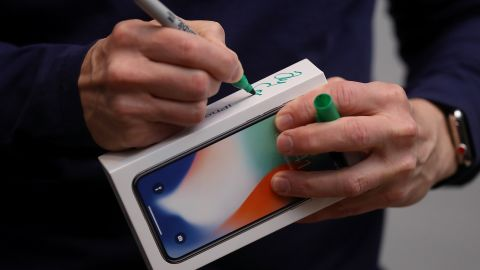 Tim Cook signs the box of a new iPhone X at an Apple Store in Palo Alto on November 3, 2017. The highly anticipated iPhone X went on sale around the world that day.