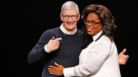 Cook and Oprah Winfrey hug during an Apple special event at the Steve Jobs Theater in Cupertino on March 25, 2019.