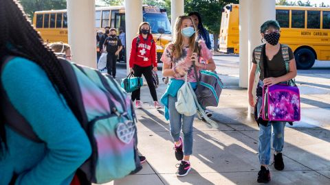 Students arrive by bus for the first day of school at Kernodle Middle School in Greensboro, N.C., on Monday, Aug. 23, 2021. The federal government has provided $190 billion in pandemic aid to schools since March 2020. This is more than quadruple what the U.S. Education Department spends on K-12 schools in a typical year. (Woody Marshall/News & Record via AP)
