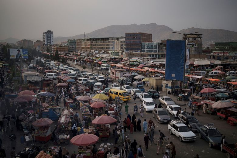 Cars wait in traffic as Afghans shop in a local market in Kabul, Afghanistan, Saturday, Sept. 11, 2021.