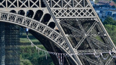 TOPSHOT - French highliner Nathan Paulin performs on a 70-metre-high slackline spanning 670 metres between the Eiffel Tower and the Theatre National de Chaillot, as part of the 38th European Heritage Days and the launch of the Cultural Olympiad in Paris, on September 18, 2021. - From the first floor of the Eiffel Tower to the Theatre National de Chaillot, the performance is the longest highline crossing in an urban environment. (Photo by Alain JOCARD / various sources / AFP) (Photo by ALAIN JOCARD/AFP via Getty Images)