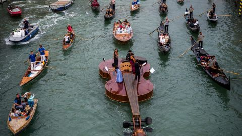 """TOPSHOT - """"Noah's Violin"""", a giant floating violin by Venetian sculptor Livio De Marchi, makes its maiden voyage for a concert on the Grand Canal in Venice on September 18, 2021. - Twelve and a half metres of wood, some of it hand-crafted, symbolizing the rebirth of Venice through art, culture and music, said the authors. The floating violin is hosting musicians from the Benedetto Marcello Conservatory playing Vivaldi. (Photo by Marco BERTORELLO / AFP) (Photo by MARCO BERTORELLO/AFP via Getty Images)"""