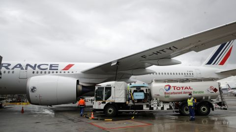 Workers refuel an Airbus A350 with sustainable aviation fuel at Roissy airport, north of Paris, on May 18, 2021. Air France-KLM is sending into the air what it calls its first long-haul flight with sustainable aviation fuel Tuesday. The plane is said to be using petroleum mixed with a synthetic jet fuel derived from waste cooking oils.