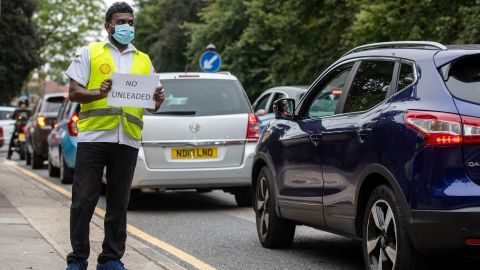 LONDON, ENGLAND - SEPTEMBER 25: A Shell garage employee holds a sign on the side of the road informing a queue of traffic that they do not have unleaded petrol on September 25, 2021 in Blackheath, London, United Kingdom. BP and Esso have announced that its ability to transport fuel from refineries to its branded petrol station forecourts is being impacted by the ongoing shortage of HGV drivers and as a result, it will be rationing deliveries to ensure continuity of supply. (Photo by Chris J Ratcliffe/Getty Images)