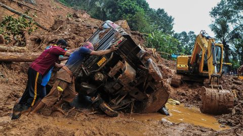 Rescue workers push a overturned vehicle stuck in the mud and debris at a site of a landslide claimed to be caused by heavy rains in Kokkayar in India's Kerala state on October 17, 2021.
