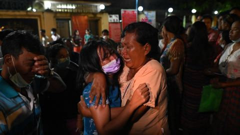 A woman is reunited with her waiting mother outside the Insein Prison following her release in Yangon on October 18, 2021, after authorities announced more than 5,000 people jailed for protesting against a February coup which ousted the civilian government would be released. (Photo by STR / AFP) (Photo by STR/AFP via Getty Images)