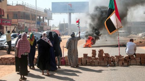 """Sudanese protesters lift national flags next to a brick roadblock during a demonstration in the capital Khartoum, on October 25, 2021, to denounce overnight detentions by the army of members of Sudan's government. - Armed forces detained Sudan's Prime Minister over his refusal to support their """"coup"""", the information ministry said, after weeks of tensions between military and civilian figures who shared power since the ouster of autocrat Omar al-Bashir. (Photo by AFP) (Photo by -/AFP via Getty Images)"""