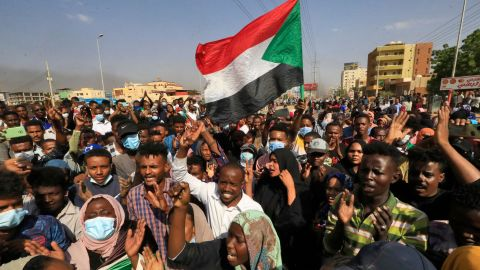 """TOPSHOT - Sudanese protesters lift national flags as they rally on 60th Street in the capital Khartoum, to denounce overnight detentions by the army of government members, on October 25, 2021. - Armed forces detained Sudan's Prime Minister over his refusal to support their """"coup"""", the information ministry said, after weeks of tensions between military and civilian figures who shared power since the ouster of autocrat Omar al-Bashir. (Photo by AFP) (Photo by -/AFP via Getty Images)"""