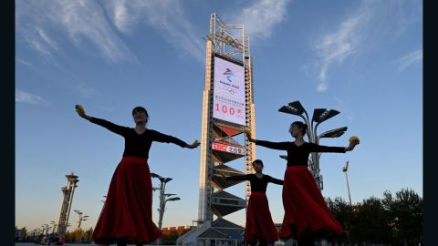 Dancers perform in front of the countdown clock showing 100 days until the opening of the 2022 Beijing Winter Olympics, at the Olympic Park in Beijing on October 27, 2021. (Photo by Noel Celis / AFP) (Photo by NOEL CELIS/AFP via Getty Images)